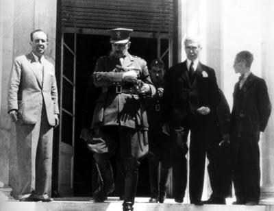 Ο στρατηγός Τσολάκογλου αμέσως μετά την ορκωμοσία του, στην έξοδο του Πολιτικού Γραφείου. Τον ακολουθούν στα αριστερά του ο νέος υπουργός Εθνικής Οικονομίας Πλάτων Χατζημιχάλης και ο στρατηγός Γεώργιος Μπάκος. Εκατέρωθεν πολιτικοί συντάκτες της εποχής (δεξιά ο Γ. Ασημάκης).