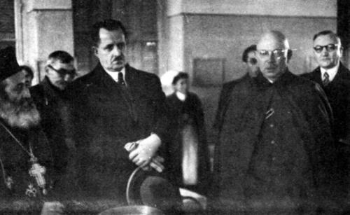 Η φτωχική τελετή των Θεοφανείων στον Πειραιά τον Ιανουάριο 1942. Αριστερά ο Τσολάκογλου και στο άκρο δεξιά ο στρατηγός Σωτήριος Μουτούσης, υπουργός Συγκοινωνίας. Παρίσταται ανώτερος Γερμανός αξιωματικός, ως εκπρόσωπος των γερμανικών στρατιωτικών αρχών κατοχής.